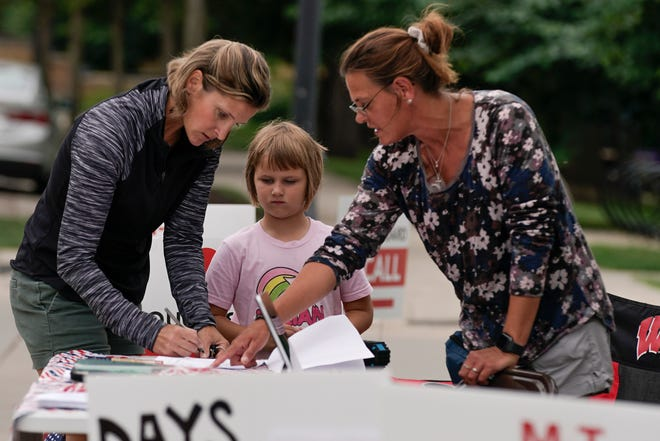 Kimberly Klimek with her daughter Lily sign a petition to recall the entire Mequon-Thiensville School District board outside the Mequon Library Monday, Aug. 23, 2021, in Mequon, Wis.